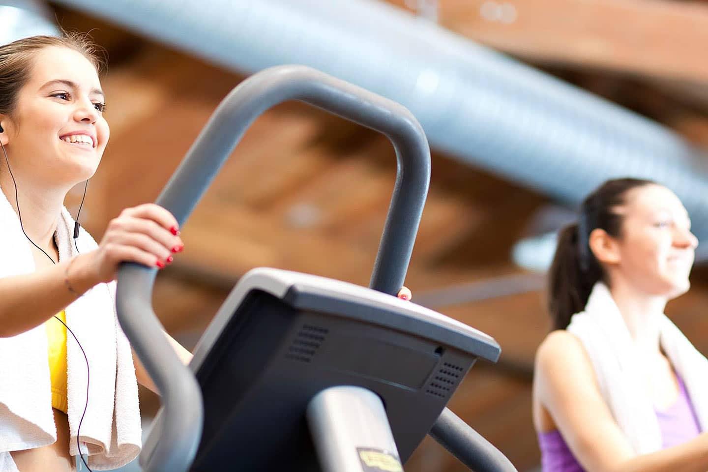 Ženska na eliptiku v fitnesu